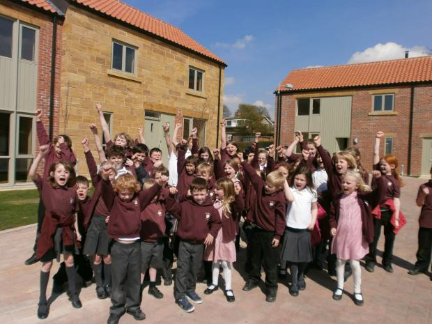 Darlington and Stockton Times: Children from Osmotherley School Primary School celebrate the opening of the award-winning affordable housing development