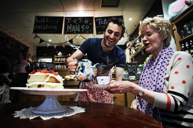 Comedian Patrick Monahan serves up tea at The Olde Young Tea House, in Middlesbrough, to customer Ann Hyman. Picture: Stuart Boulton