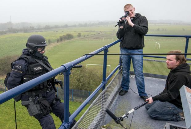 Captions: James Bushnall videos an armed police officer as he abseils into action while Kyle Dollard captures the sound