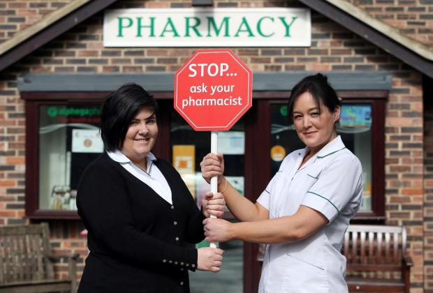 ASK THE PHARMACIST: (L-R) Counter assistant Sarah Littlefair and pharmacy technician Vicky Icke with lollipop sign.Picture: CHRIS BOOTH