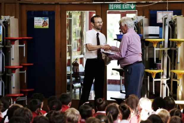 Darlington and Stockton Times: BOOK DONATION: Doreen Dean's son Dave Dean hands over copies of the late author's books to Abbey School headteacher George Ford. Picture: STUART BOULTON