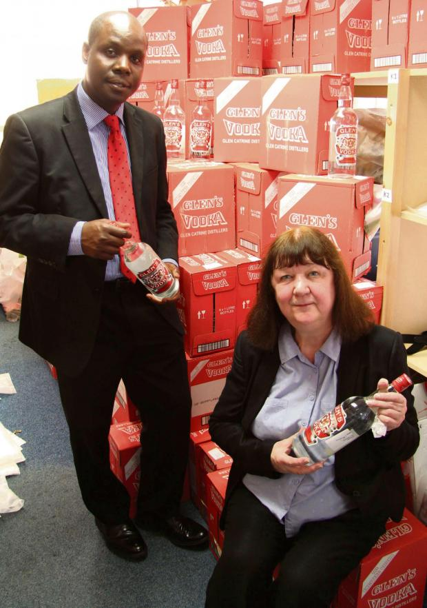 Darlington and Stockton Times: Edward Kunonga, Middlesbrough Council's director of public health with Councillor Julia Rostron with the mountain of seized counterfeit vodka.