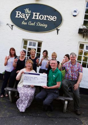 COMMUNITY FUNDRAISING: A local community group in Heighington have raised over £1200 for Macmillan cancer support, pictured front Sue Flint presents the cheque to  Macmillan volunteer Kevin Richardson  Picture: SARAH CALDECOTT