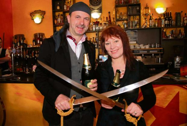 CHAMPAGNE SLICE: Voodoo Cafe owners Les and Kendra Fry  become sabreurs at a ceremony in Darlington. Picture: ANDY LAMB