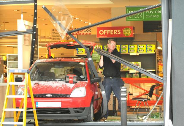 Darlington and Stockton Times: A workman attempts to remove some of the framework of the window at Waitrose in York after a driver accidently reversed her car through it. Picture: Garry Atkinson