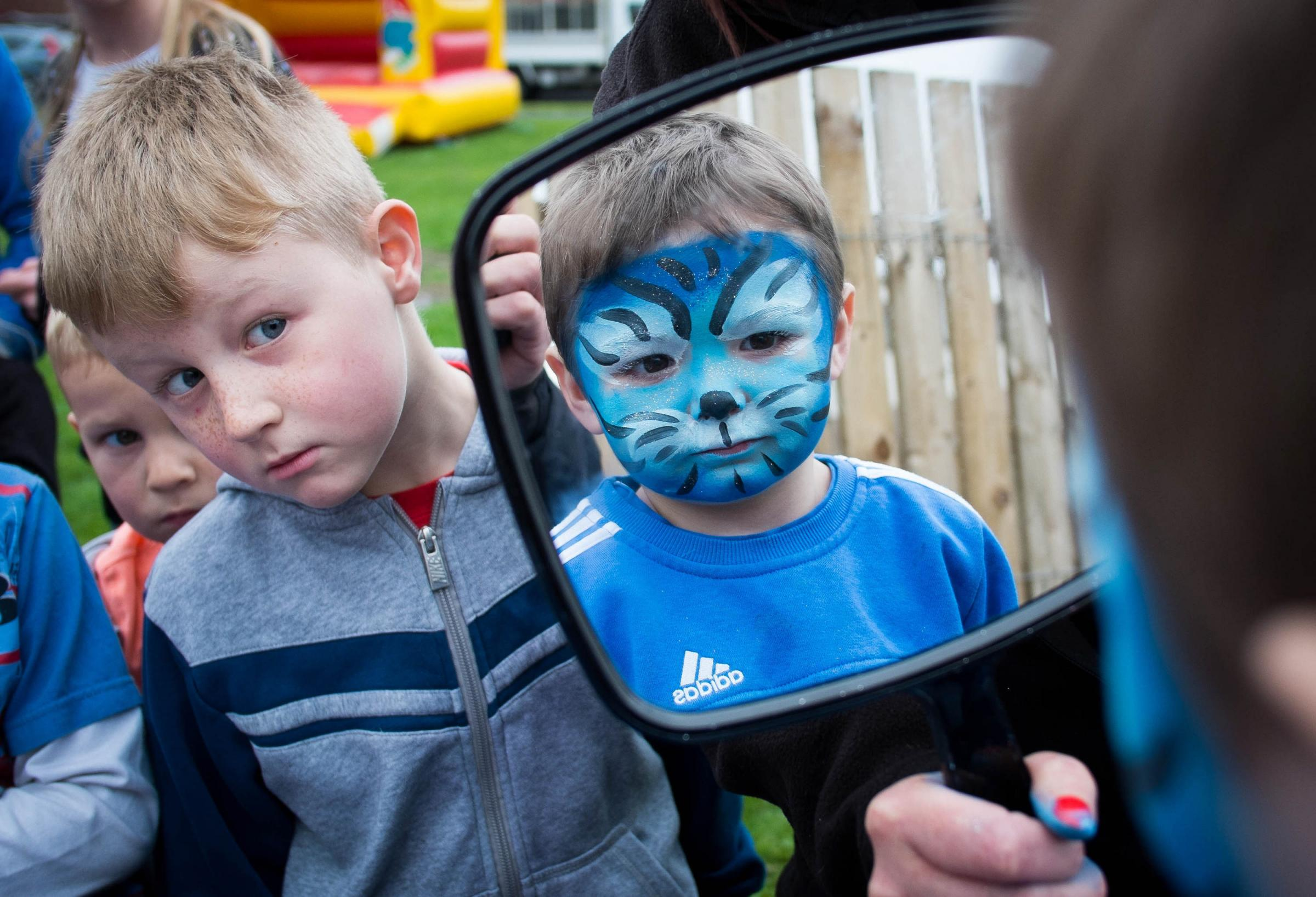 Mason Cameron, 3, from Middlesbrough takes a look in the mirror after having his face painted as his friends look on as they visit the launch of this year's Easter arson campaign by Cleveland Fire Brigade
