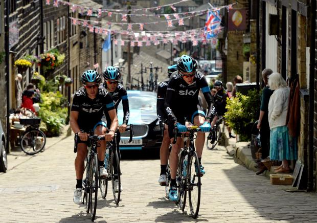 Team Sky's Chris Froome (front right) rides alongside Richie Porte as they climb the cobbled hill at Haworth - part of the route for Stage 2 of the Tour de France. John Giles/PA Wire.