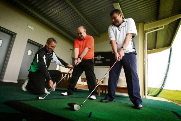 Darlington and Stockton Times: HELP FOR HEROES: Golfers from Catterick-based Phoenix House Recovery Centre, Paul Nichol, centre, and Ges Almond, right, get some tips from Rockliffe golf pro Martyn Stubbings      Picture:TOM BANKS