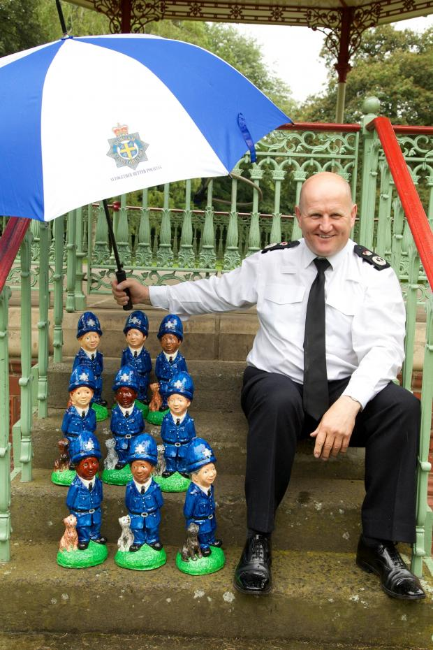 Darlington and Stockton Times: CRIME FIGHTERS: Chief Constable Mike Barton shields his gnomies from the rain Picture: KEITH TAYLOR