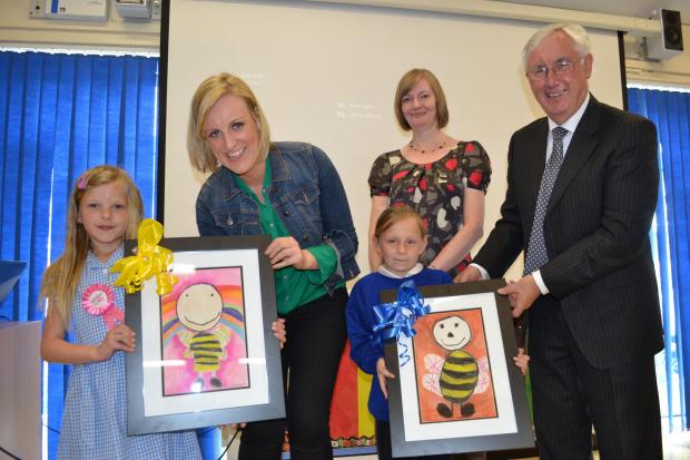 Principal, Susan Dawson (background) watches Year 3 pupils, Ebony Eastwood (left) and Milly Potts (right) present the BBC's Steph McGovern and Les Walton, chair of the Northern Education Trust with artwork to mark their visit to Norton Primary Acade