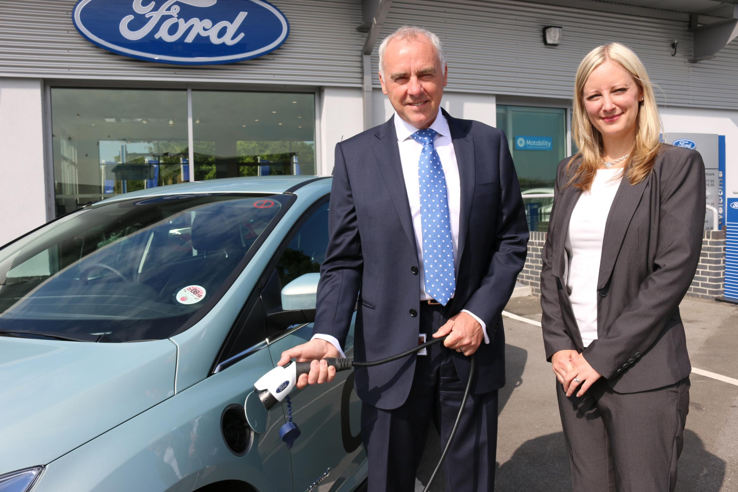 ON CHARGE: Broadacres' Property Director Paul Lightfoot charges the car with Hazel Coupe, marketing manager at RMB Automotive.