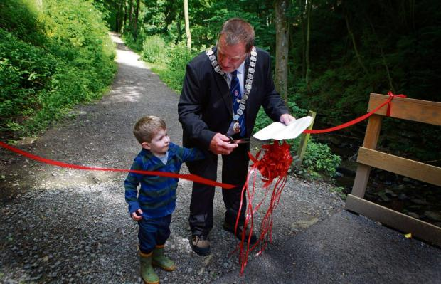 Darlington and Stockton Times: FLATTS WOOD: Barnard Castle Mayor John Blissett with grandson Isaac John Blissett, aged two, performs the ribbon cutting to mark the completion of improvements to Flatts Wood Picture: SARAH CALDECOTT