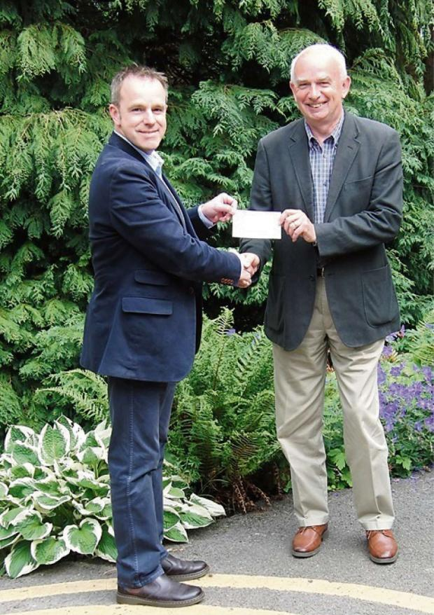 Darlington and Stockton Times: CHARITY FUNDS:Major Barney Barnbrook, left, receives a cheque from Peter Bickley, from John Weymes Racing.