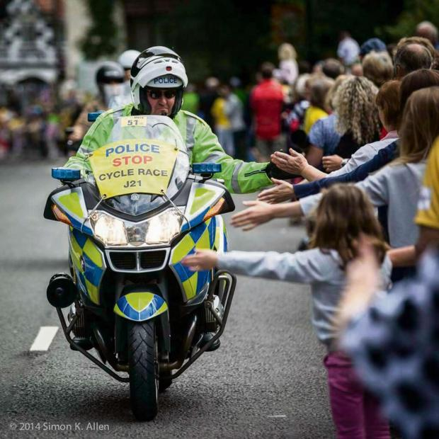 Darlington and Stockton Times: HIGH FIVES: A police outrider during the Tour de France helps keep the waiting crowds occupied