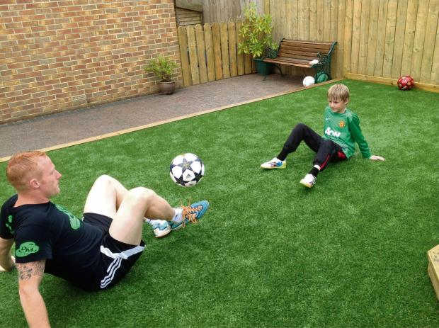 SKILLS SESSION: Football freestyler Dan Magness coaches Max Lawson, ten, in his back garden