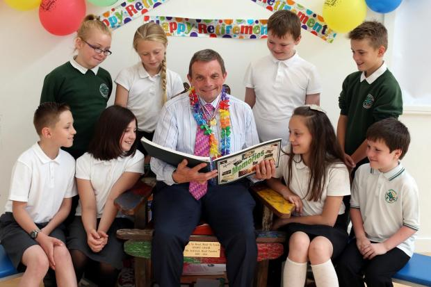 A FOND FAREWELL: Headteacher David Ackroyd is retiring from Northwood Primary School on Pendleton Road, Darlington.  Pictured sat in his story telling chair with pupils (back) Chloe Whelan (11), Carla Cooper (11) Reece Earle (11), Jack Bray (11)