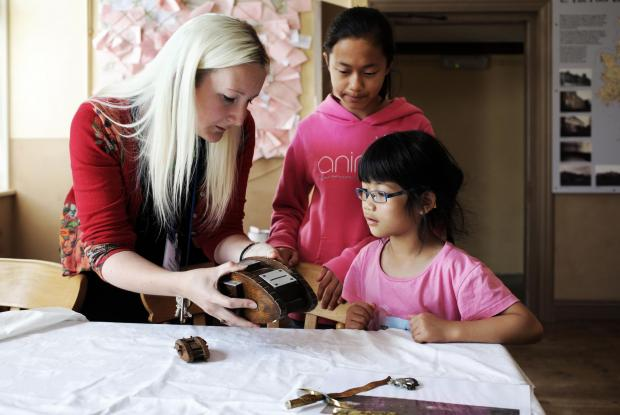 WARTIME OBJECTS: Martha and Catherine Johnson being shown a toy tank money box by learning officer Naomi Parsons during a wartime object handling session at the Workhouse Museum in Ripon. Picture: STUART BOULTON
