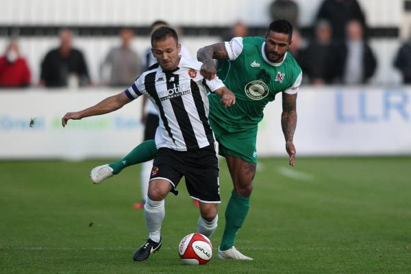 DERBY BATTLE: Spennymoor's Lewis Dodds is put under pressure by Darlington's Leon Scott