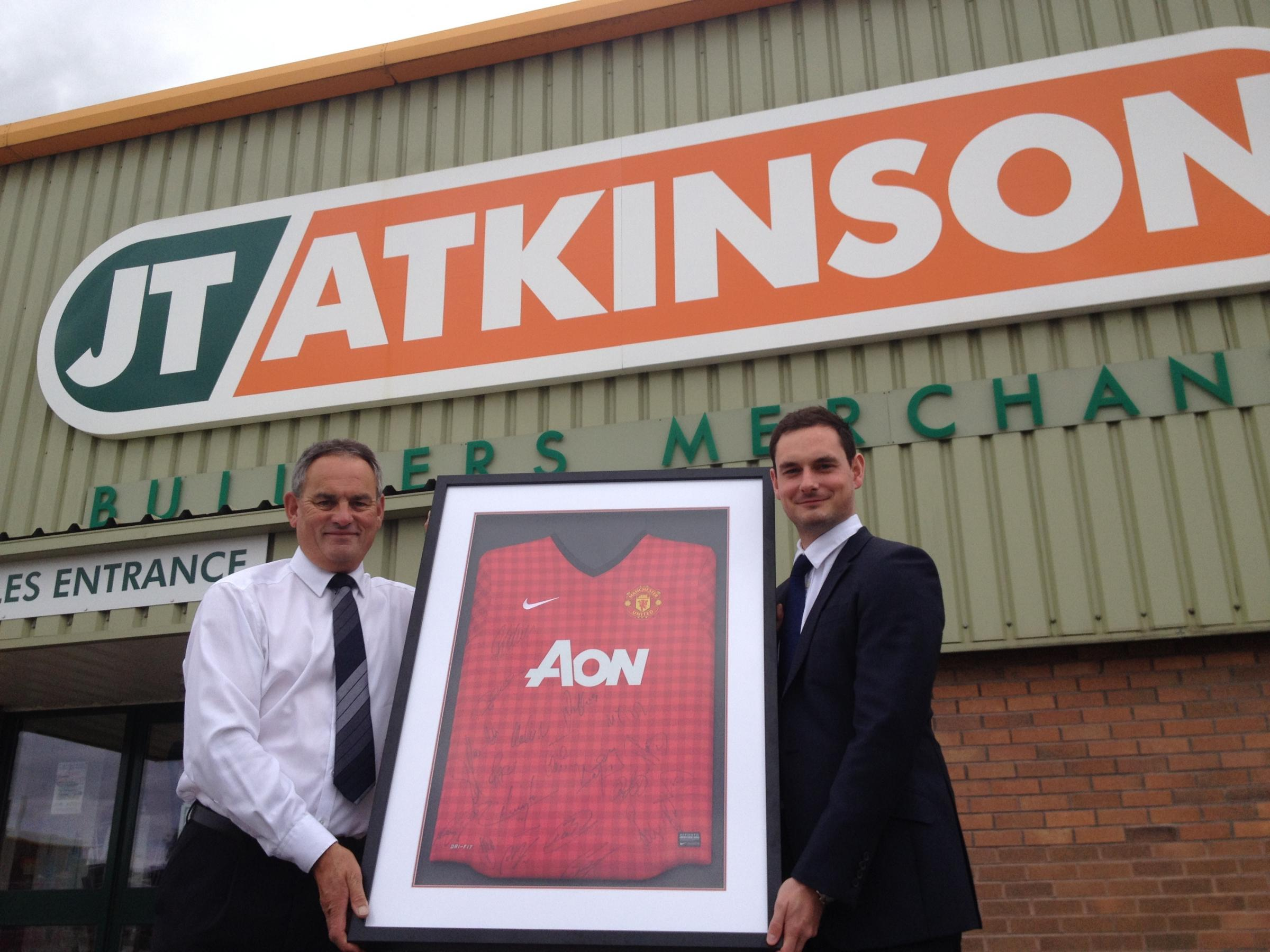 FUNDING GOAL: Jamie Atkinson, sales director of JT Atkinson hands over the Manchester United shirt to event co-organiser Peter Kirkbride