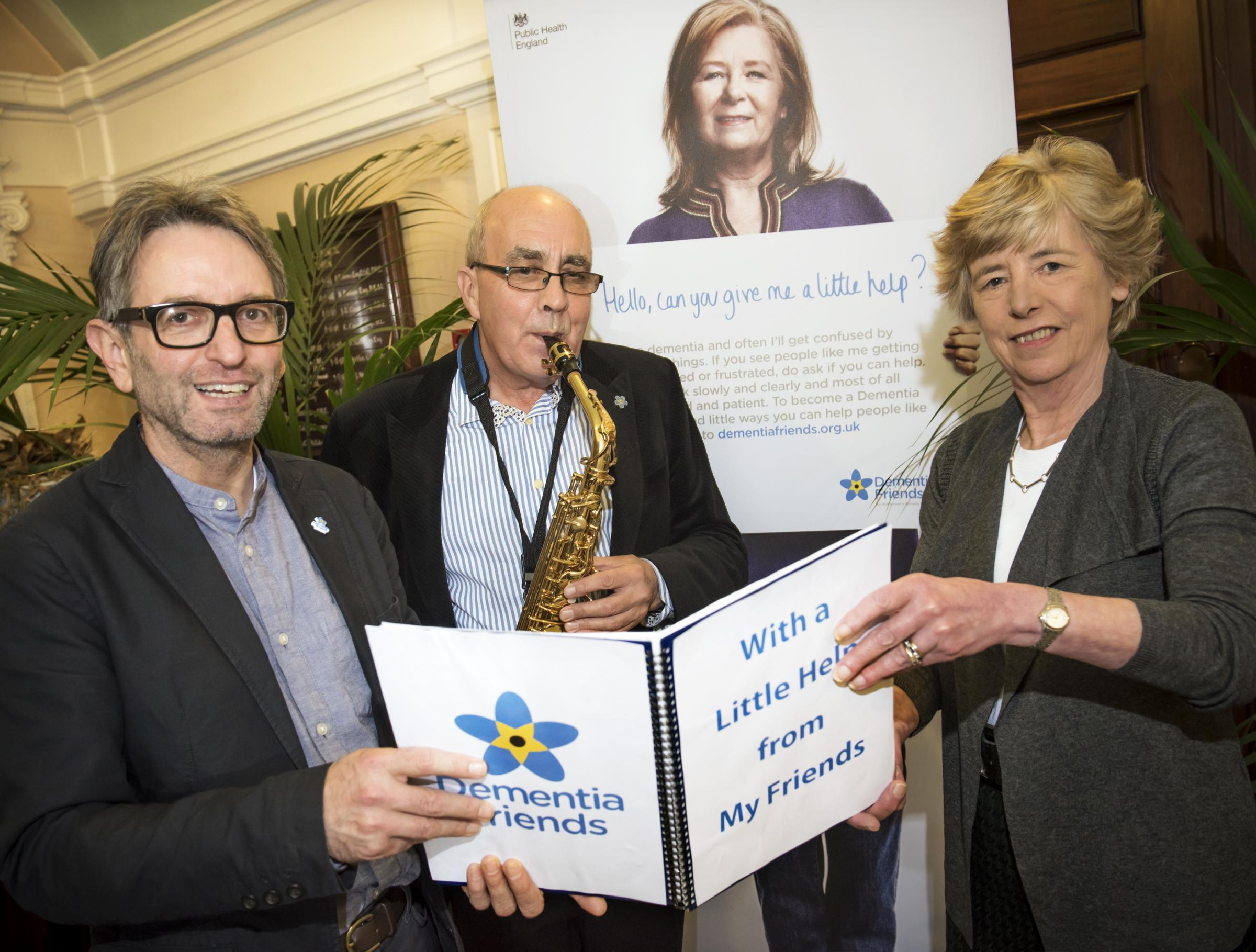 DEMENTIA FRIEND: Councillor Clare Wood and 600th Dementia Friend Martin Feekins listen to Chris Riley playing 'With a little help from my friends'.