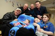 INSPIRATIONAL: Roy 'Chubby' Brown and others visit Zoe's Place Hospice in Normanby prior to a charity night in April at Eston Labour Club.  Pictured are Roy 'Chubby' Brown, singer Keith 'The Voice' Hammersley, one-year old Amber Smith, comedian Mick Monro