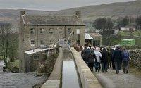 Darlington and Stockton Times: WELCOME: The first visitors walk towards Gayle Mill on Tuesday