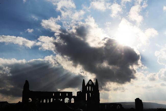 Rays of sunlight shine through Whitby Abbey – but do its bells still sometimes toll out at sea?