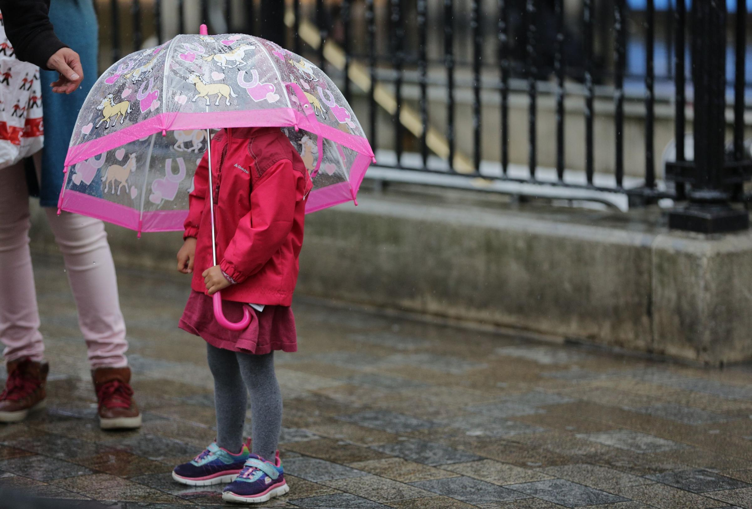 A child shelters under an umbrella. Picture: Daniel Leal-Olivas / PA Wire