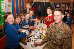 FAIRTRADE: Eleven-year-old Isabel Foster gives soldier Daniel Edwards a welcome cuppa at the Leyburn primary evfent