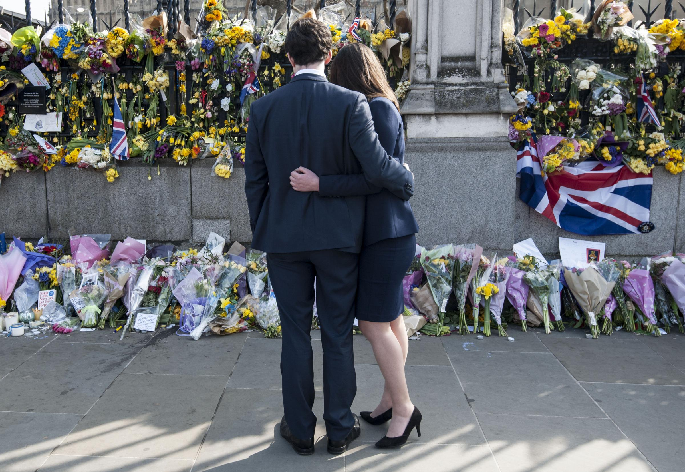 A couple look at floral tributes to the victims of the Westminster terrorist attack outside the Palace of Westminster, London. Picture: Lauren Hurley/PA Wire