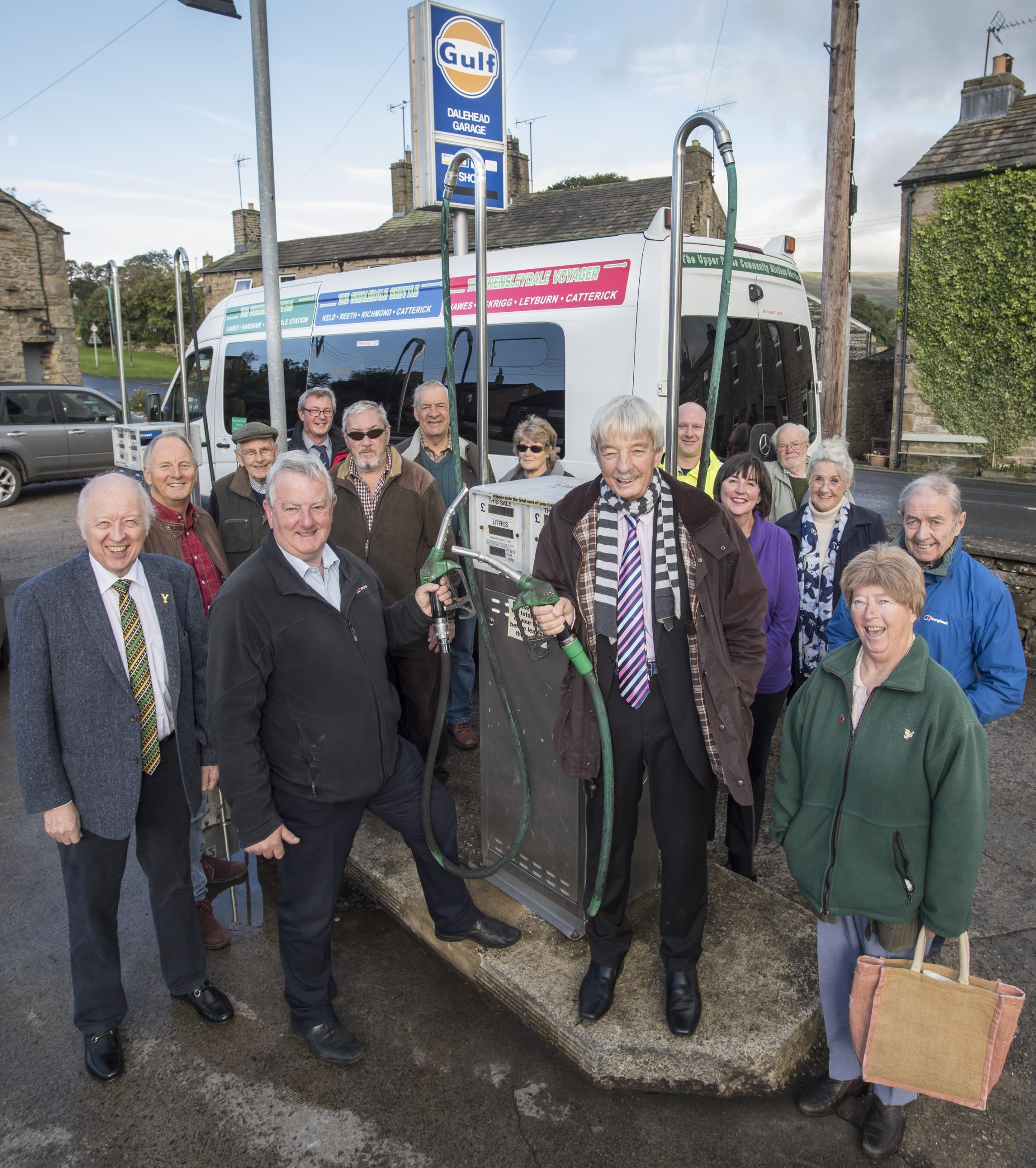 : Cllr John Blackie (centre) at the Hawes filling station with Cllr Carl Les, (far left), North Yorkshire's Leader, volunteer drivers of the Little White Bus and Upper Dales residents