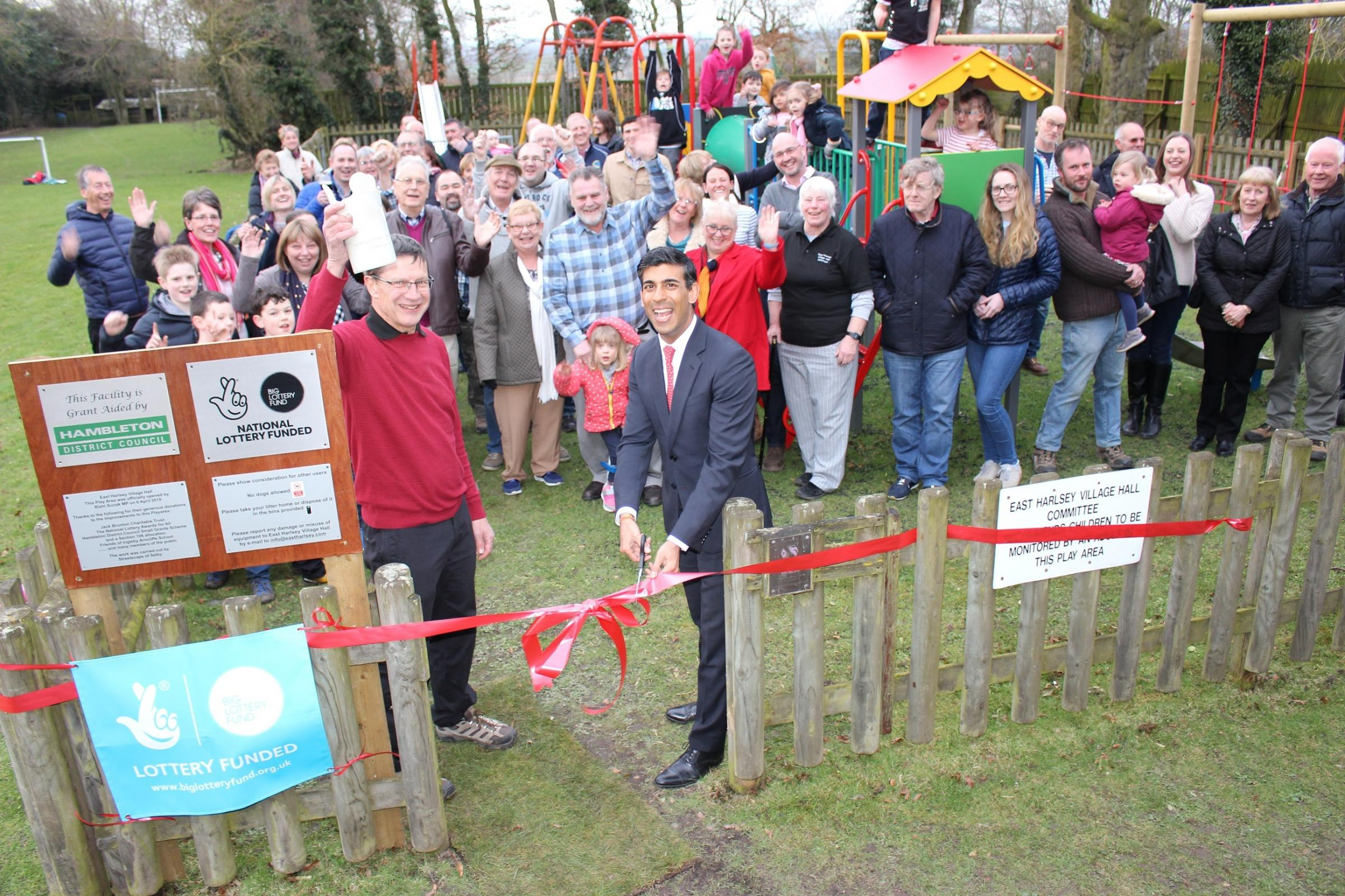 BIGGER: Rishi Sunak declares the improved play area open with Richard Martin, chairman of the village hall hall committee, and villagers.
