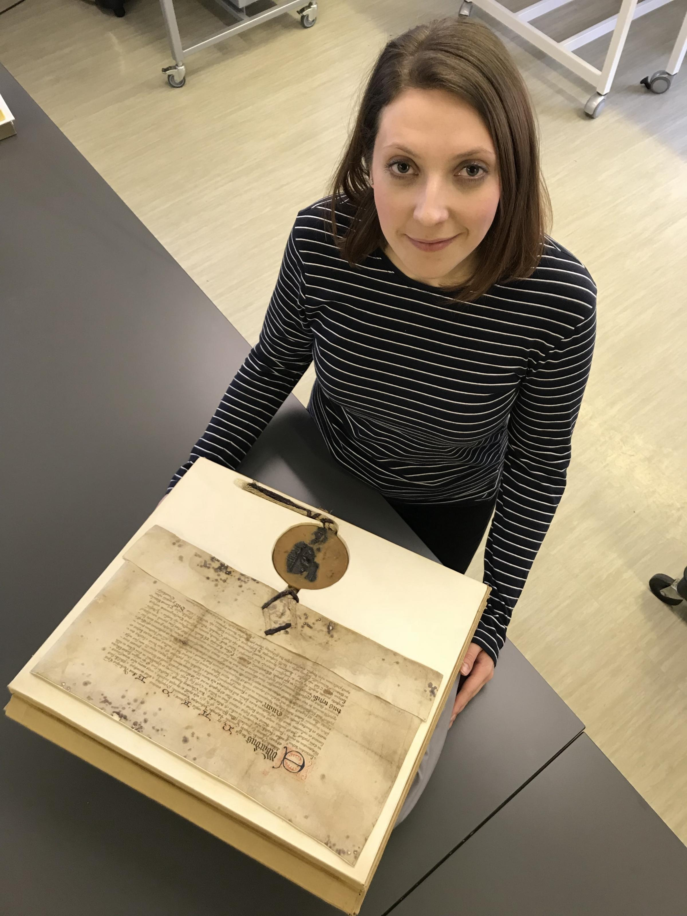 SURVEY: One of the many historic documents preserved by the County Record Office. Emily Ward, record assistant, with a grant bearing the great seal of Edward IV.