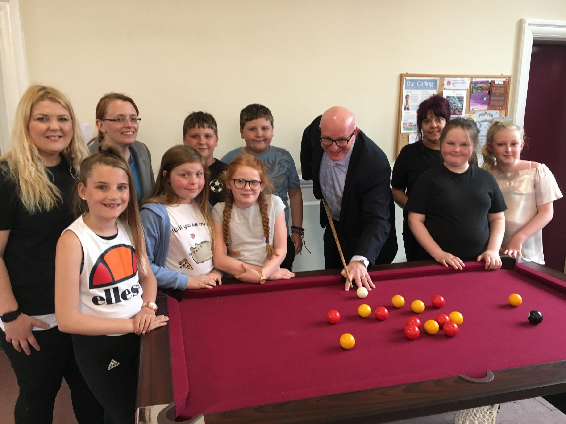 DEAL: Andy Powell, with pool cue, and Abigail Homer, third from the right, with staff from Broadacres and The Clock and children who attend the Little Hands youth club in Thirsk.
