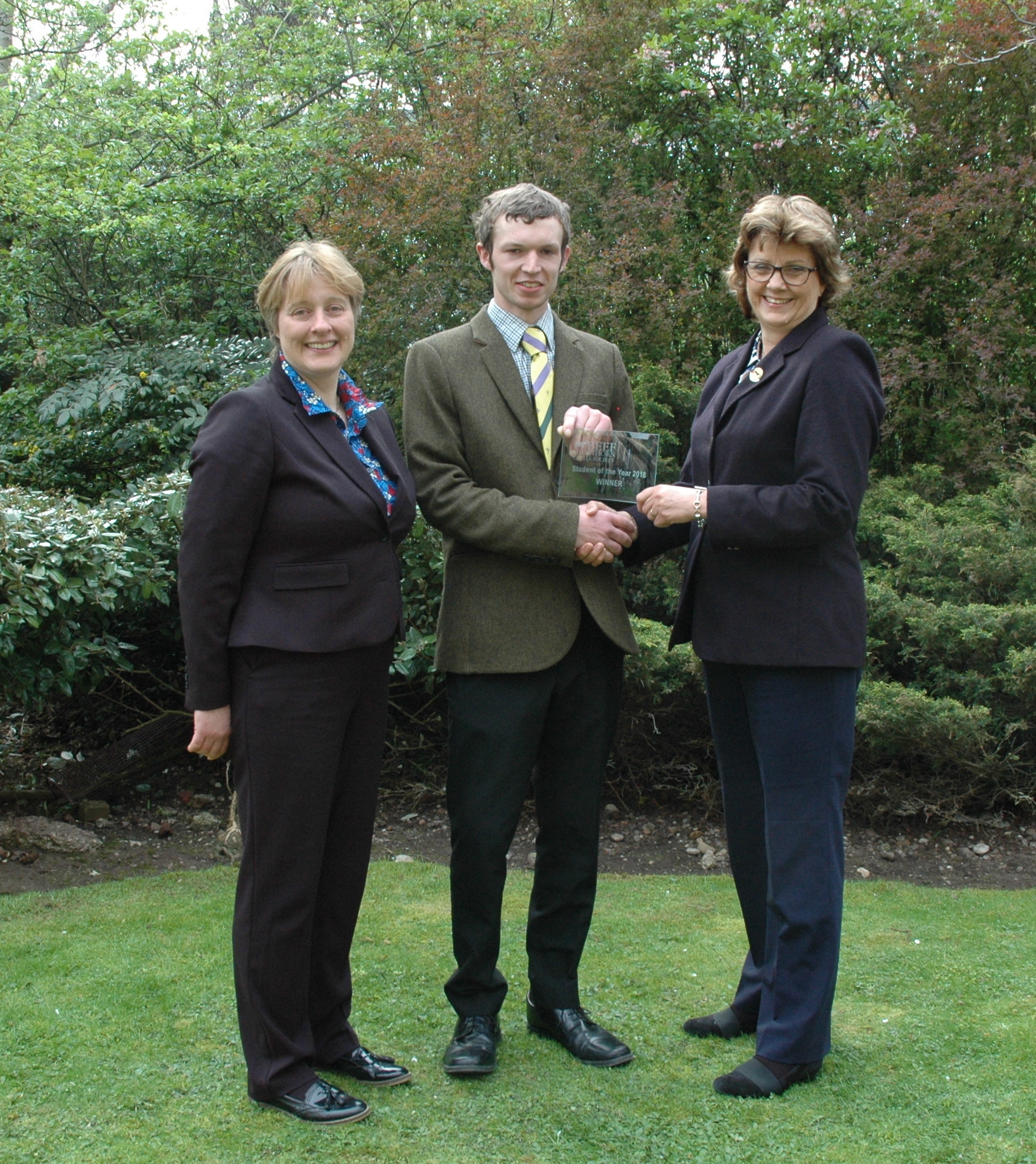 Charlie Smith receives his award from Beef Shorthorn Cattle Society president, Sally Horrell, with Askham Bryan College course tutor, Linda Lloyd