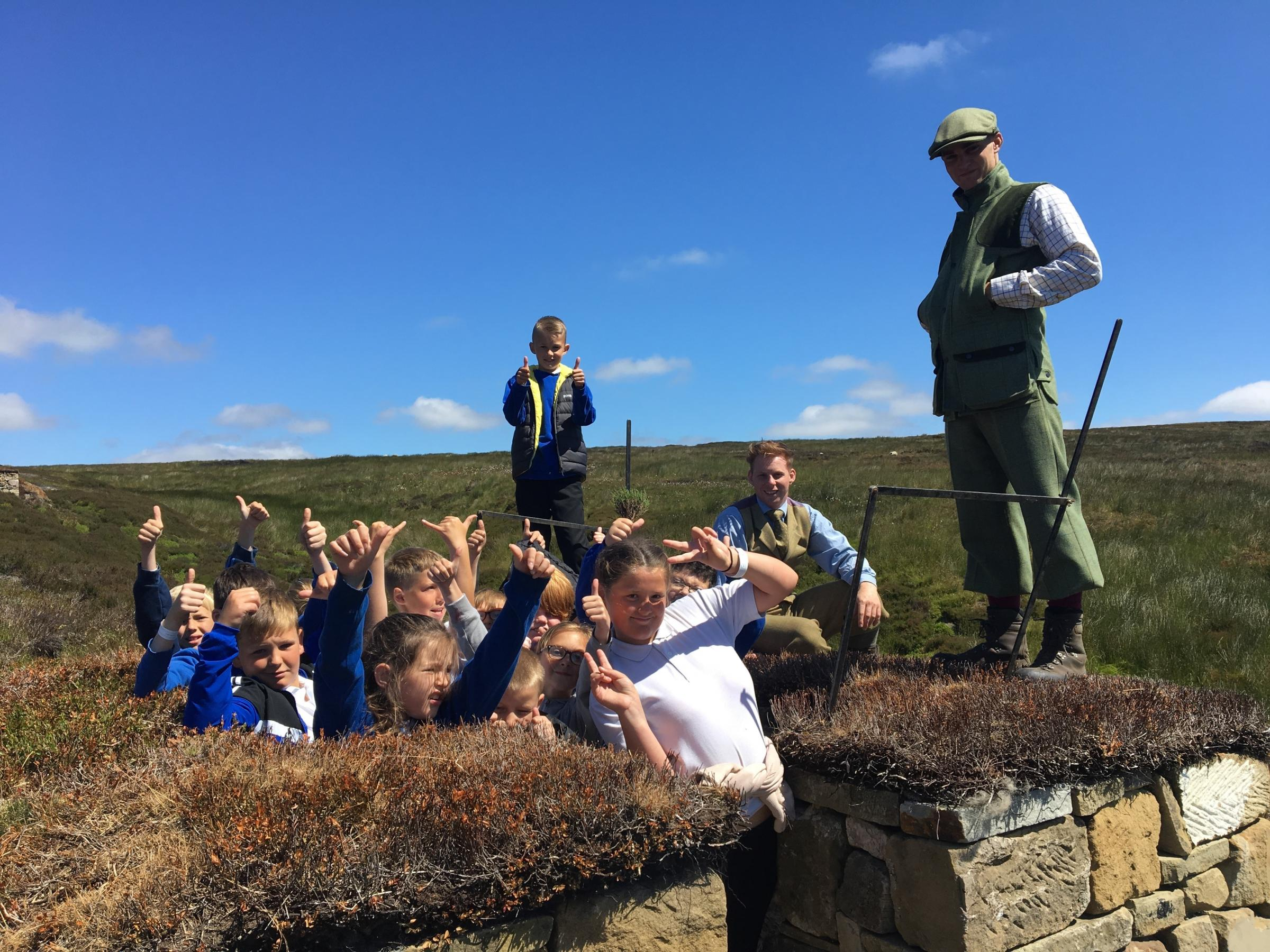 Schoolchildren in a grouse shooting butt alongside NYMMO gamekeepers
