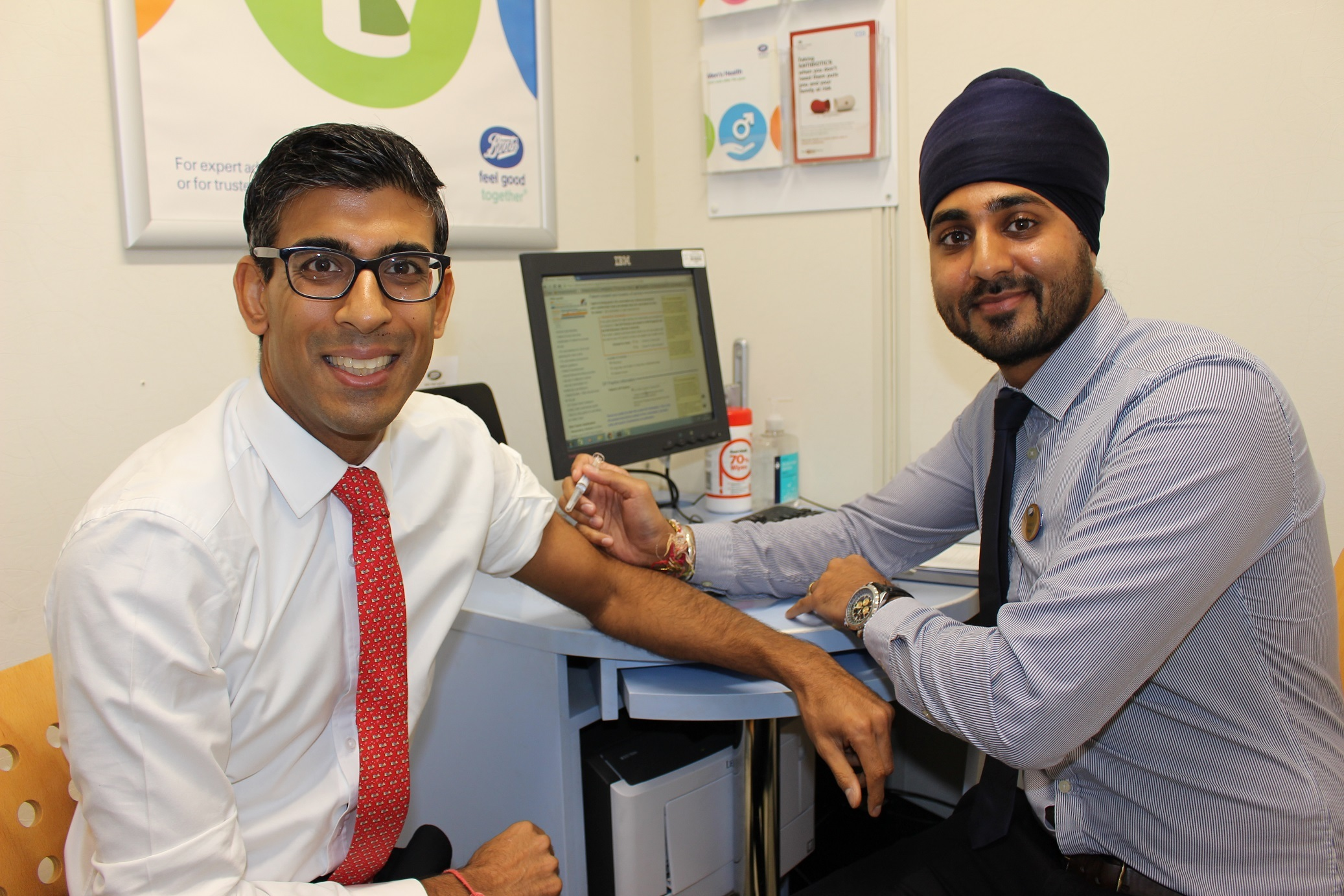 Rishi Sunak receives his flu jab from pharmacist Nicky Singh