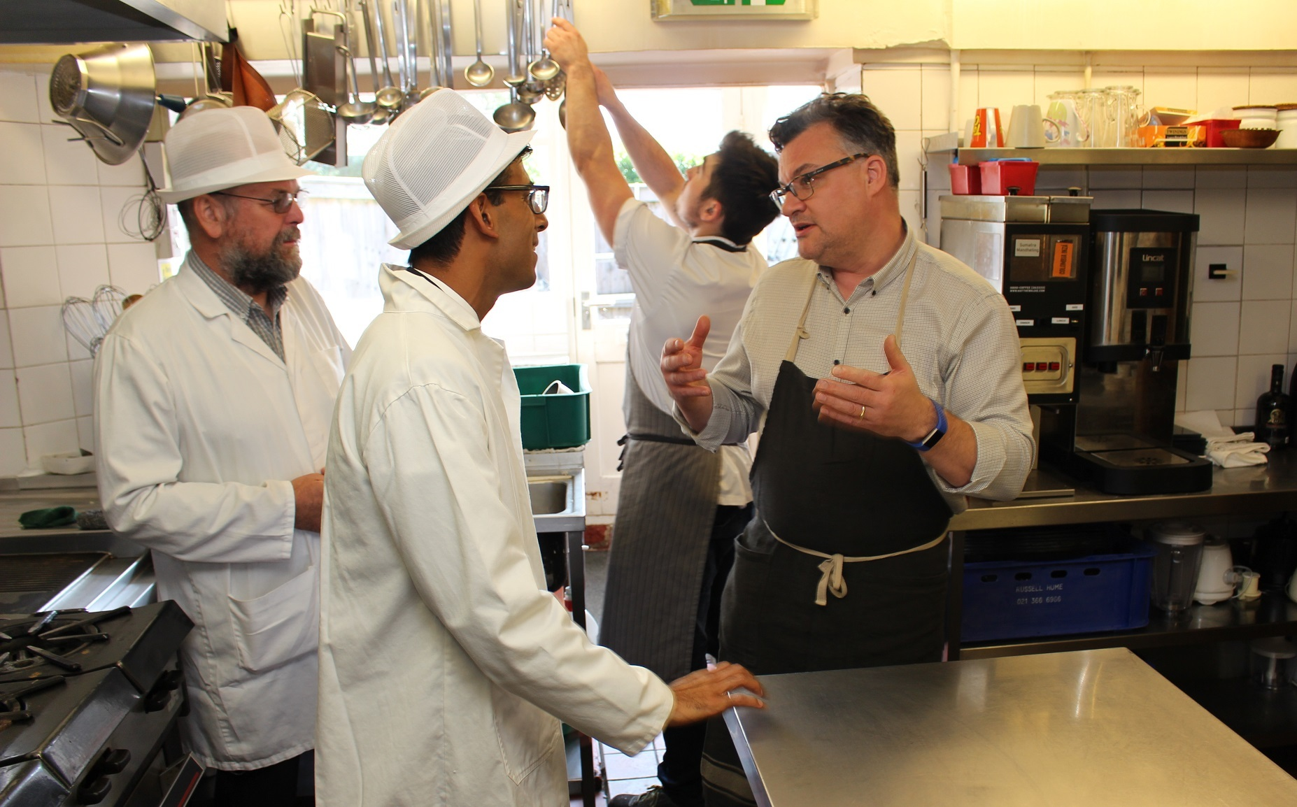 MP Rishi Sunak talks to chef patron Jonathan Harrison, right, in the kitchen of The Sandpiper, Leyburn, with Graham Bourne, Richmondshire District Council's food safety technician