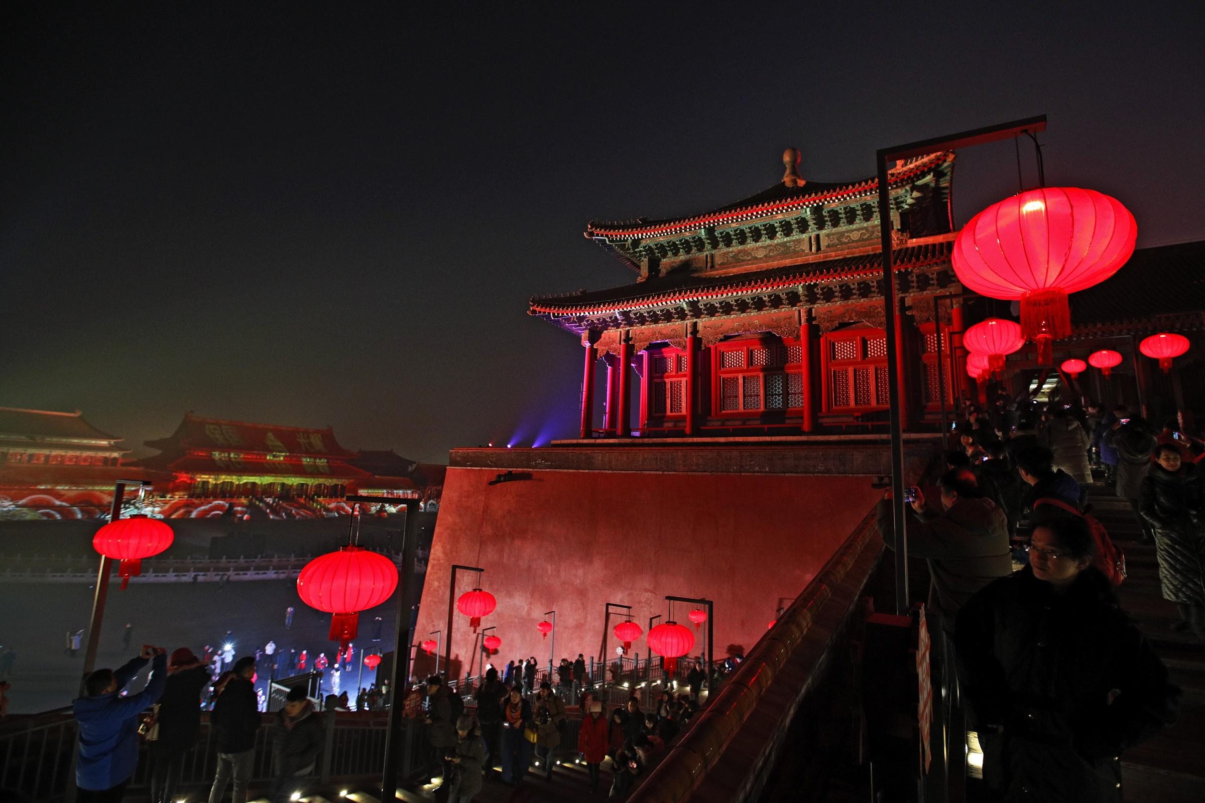 Visitors tour the Forbidden City decorated with red lanterns and illuminated with lights during the Lantern Festival in Beijing