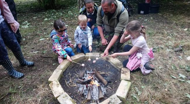 Family cooking on a campfire at Ormesby Hall