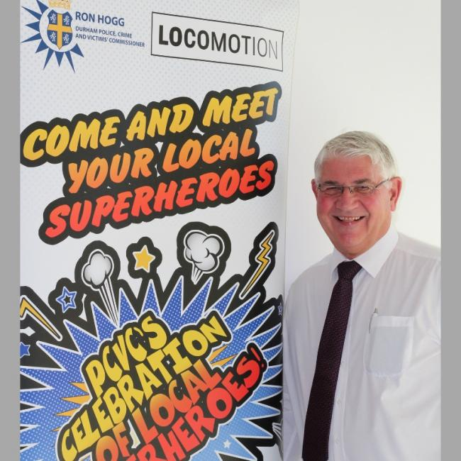 Ron Hogg with the superhero banner